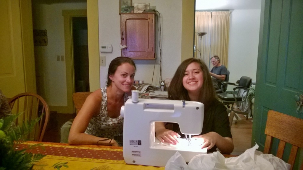 Ariana Altieri showing Maya Mendoza how to use the sewing machine